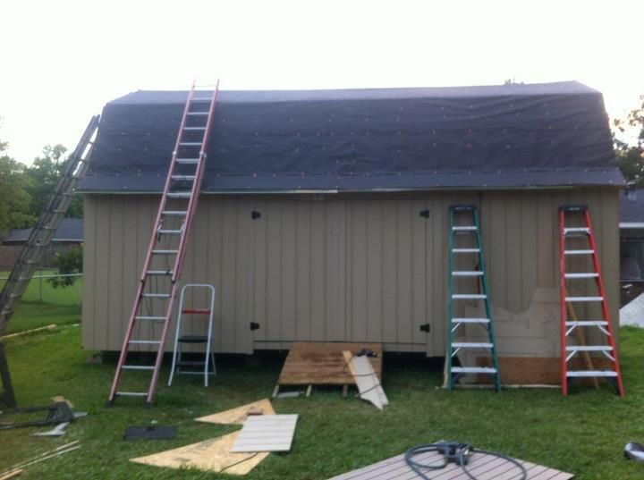 Installing felt paper on a barn shed roof.