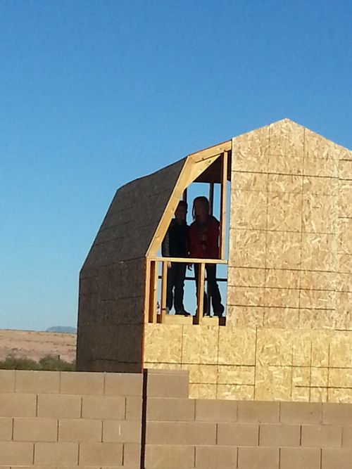 kids peeking out before last of sheeting goes on the playhouse shed